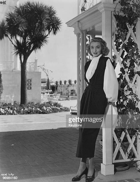 American actress Patricia Neal stars in the Warner Bros film 'The Fountainhead' 1949 She is wearing a dress designed by Milo Anderson in navy blue...