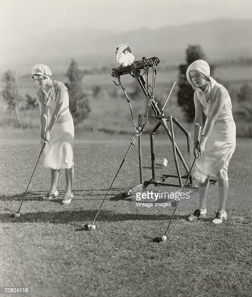 American actress Penny Singleton and another actress take lessons on their golf swings from a mechanical instructor in a scene from the musical...