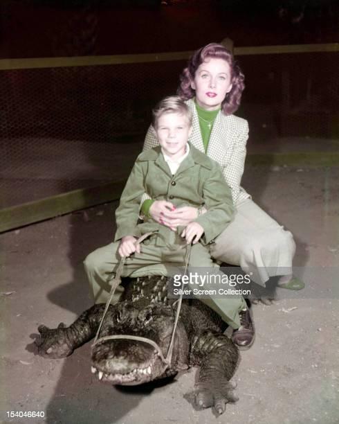American actress Rhonda Fleming and a boy probably her son Kent Lane riding an alligator circa 1955