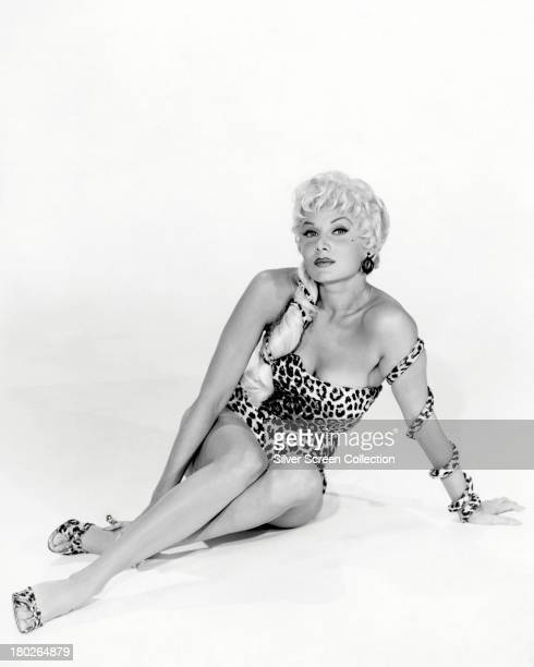 American actress Rhonda Fleming posing in a onepiece leopardprint swimsuit circa 1955