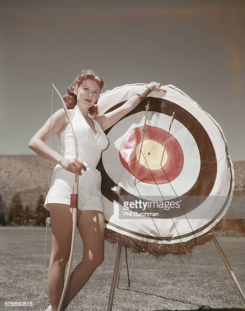 American actress Rhonda Fleming with a bow and arrow and archery target circa 1950