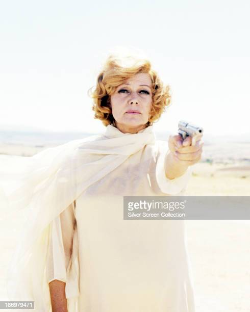 American actress Rita Hayworth aiming a pistol in a promotional portrait for 'The Bastard' directed by Duccio Tessari 1968