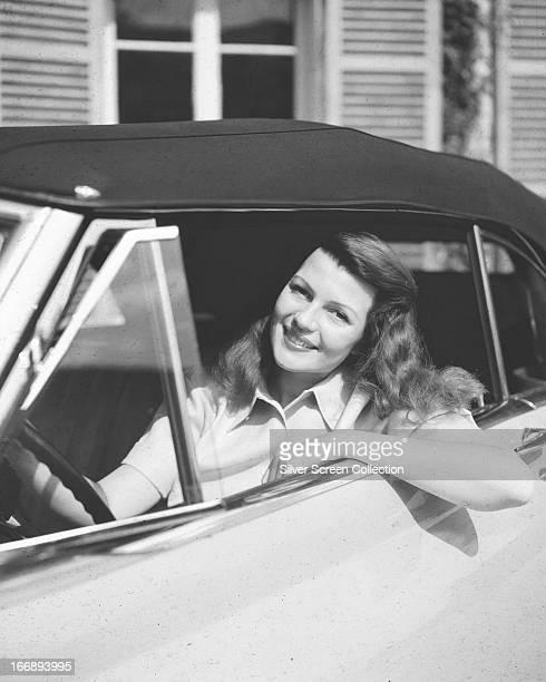 American actress Rita Hayworth at the wheel of a car circa 1940