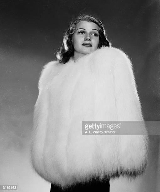 American actress Rita Hayworth encased in a fur jacket