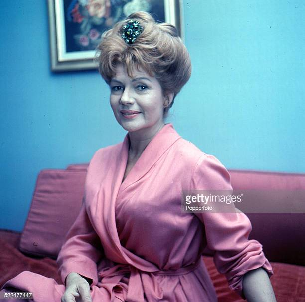 American actress Rita Hayworth pictured wearing a gown whilst sitting on a sofa in London in 1964