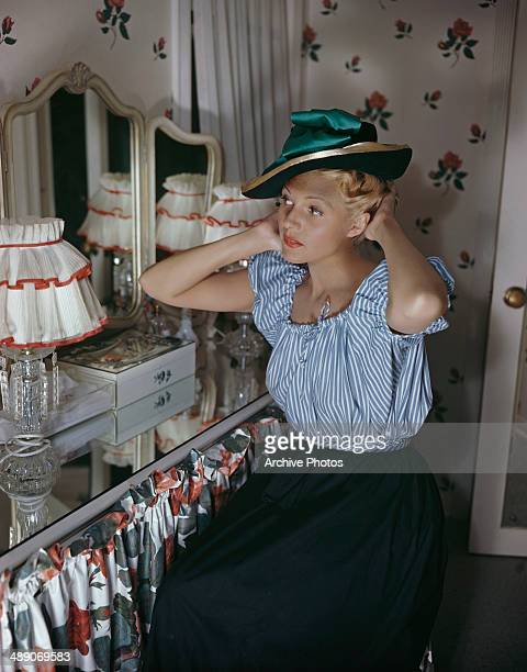 American actress Rita Hayworth tries on a hat in front of a mirror circa 1950