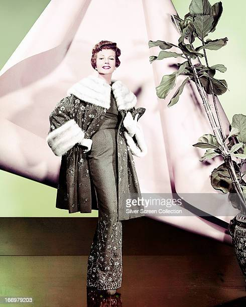 American actress Rita Hayworth wearing a green outfit with embroidered flowers and white fur trim circa 1945