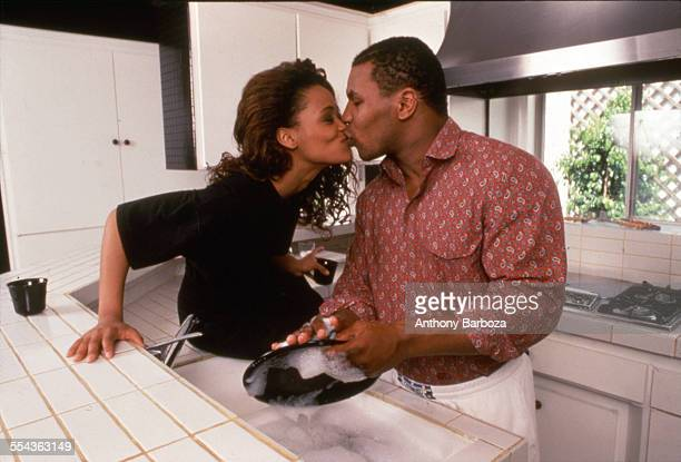 American actress Robin Givens kisses her husband heavyweight boxer Mike Tyson as he washes dishes in the kitchen of their home Los Angeles California...