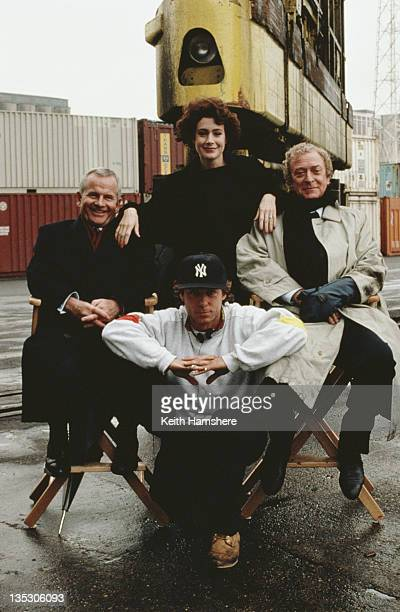 American actress Sean Young with English actors Michael Caine and Ian Holm and director Russell Mulcahy on the set of the film 'Blue Ice' 1992