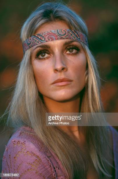 American actress Sharon Tate wearing a pink top and headband circa 1968