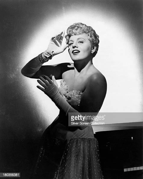 American actress Shelley Winters in an offtheshoulder evening gown and gloves circa 1955