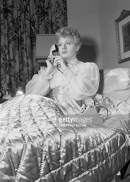 American actress Shelley Winters sits in bed and holds her hand over the receiver of a telephone in a scene from an episode of the television...
