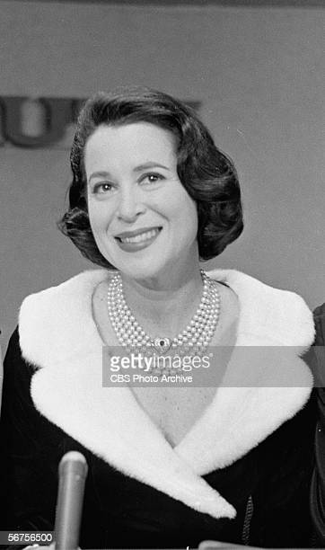 American actress socialite and television personality Kitty Carlisle dressed in a furtrimmed black top smiles from behind a microphone as a panelist...