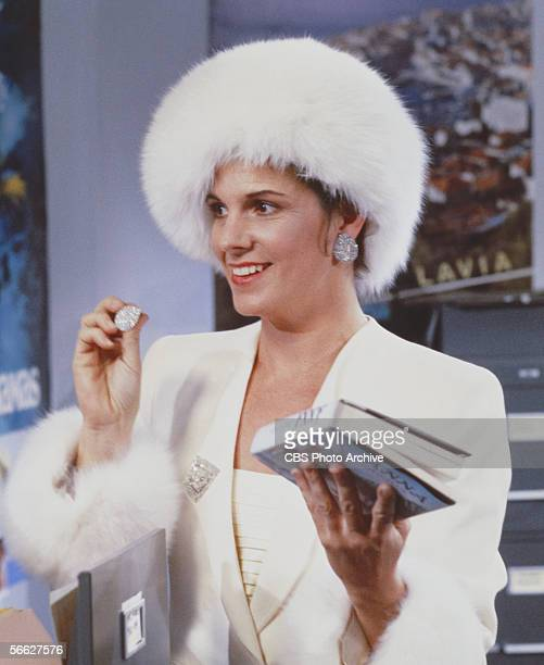 American actress Susan Saint James dressed in a Russianstyle white fur hat and matching furtrimmed jacket stands near an open file cabinet in a still...