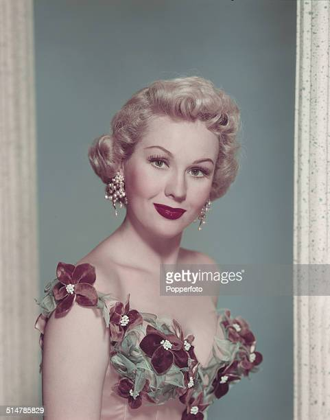 American actress Virginia Mayo posed wearing elaborate pearl ear rings and a corset dress circa 1950
