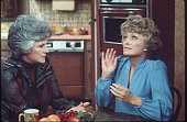 American actresses Beatrice Arthur and Rue McClanahan talk at a table in a scene from the television show 'Maude' Los Angeles California mid 1970s