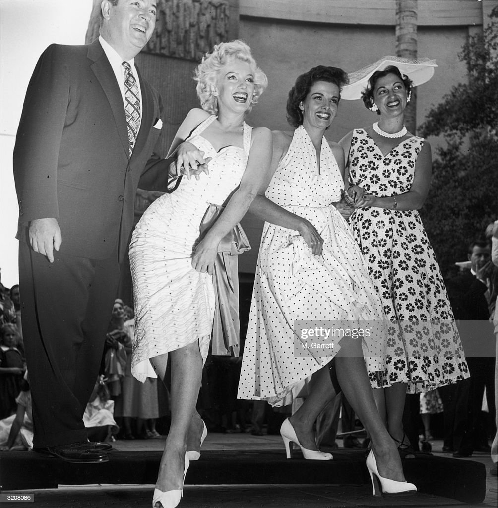 American actresses Marilyn Monroe and Jane Russell bookended by an unidentified man and woman imprint their highheeled shoes in wet cement during the...