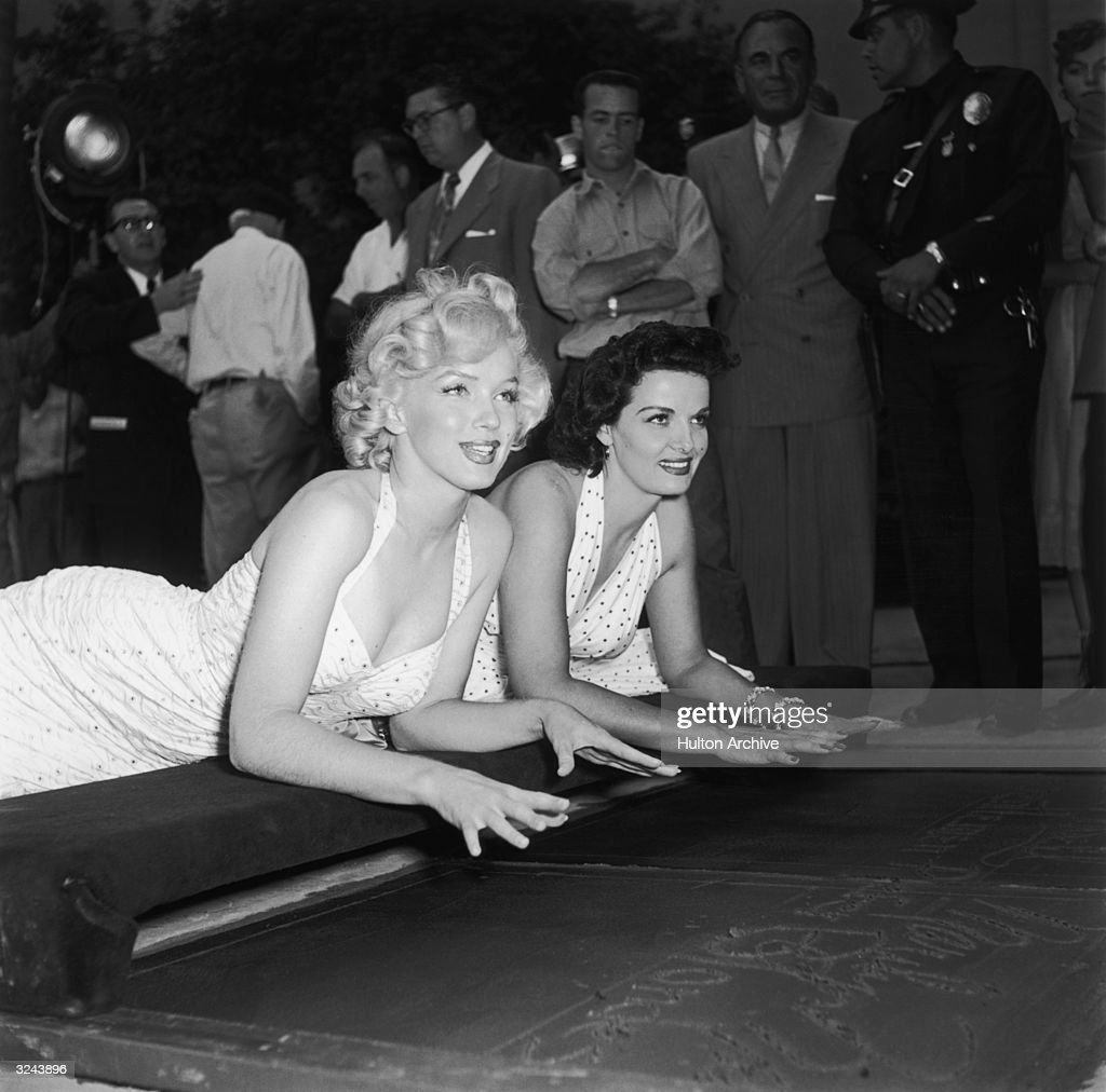 American actresses Marilyn Monroe and Jane Russell lay on their stomachs about to press their hands into wet cement at Grauman's Chinese Theatre in...