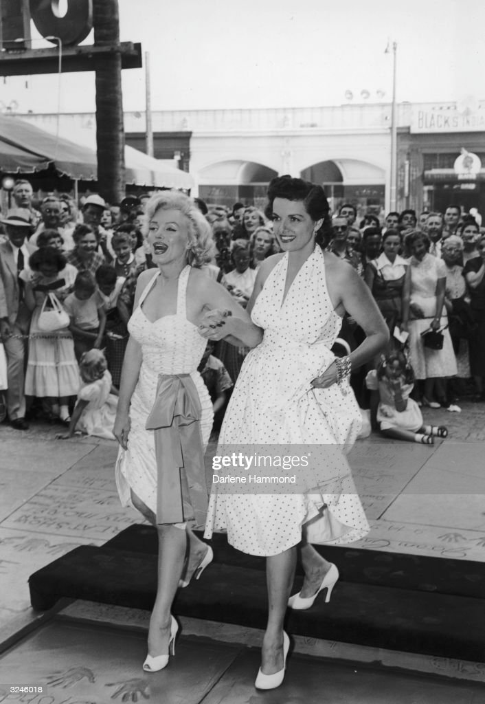 American actresses Marilyn Monroe and Jane Russell press their heel prints into wet cement in front of Grauman's Chinese Theater to promote director...