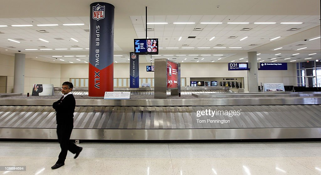 American Airlines baggage agent Roger Rajan stands in an empty baggage claim area in Terminal D after hundreds of flights were canceled at DFW International Airport on February 1, 2011 in Dallas, Texas. A major ice storm hit the Dallas/Fort Worth area overnight days before Super Bowl XLV is to be be held in Arlington, Texas.