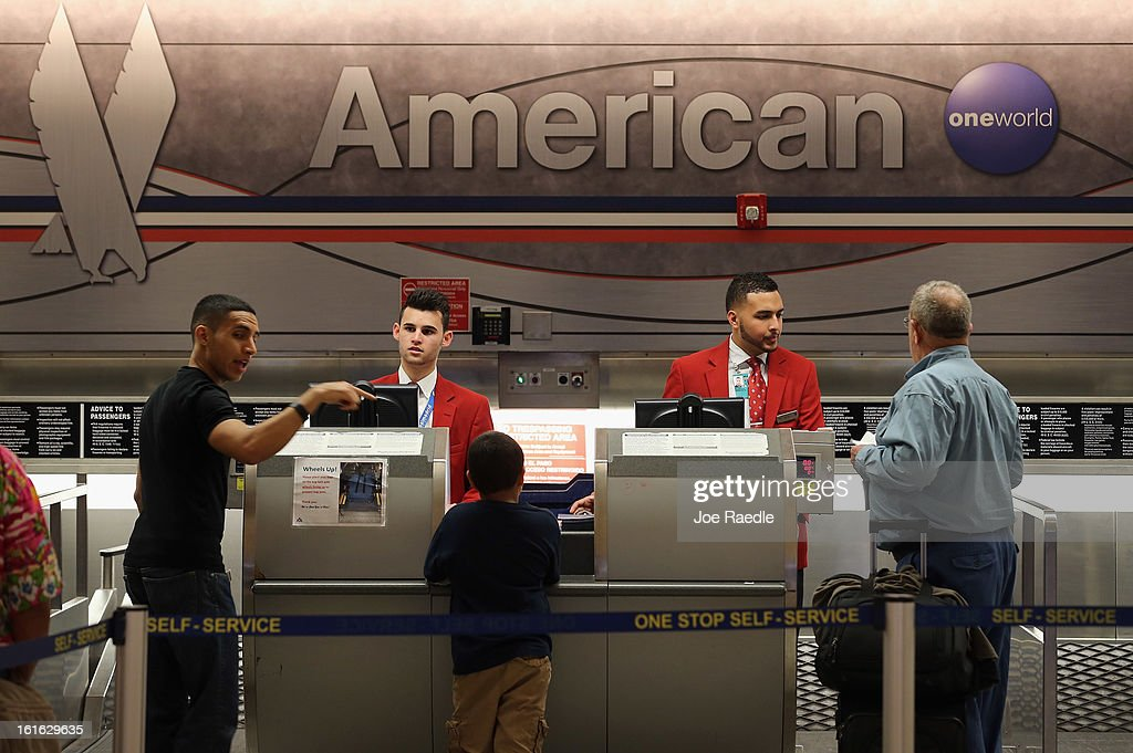 American Airlines employees help travelers at the ticket counter in the Miami International Airport on February 12, 2013 in Miami, Florida. Reports indicate that a deal between American Airlines and US Airways to merge is set to be announced as early as tomorrow. If the deal goes through it would create the world's biggest airline.
