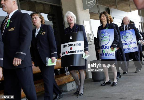 American Airlines flight attendants carry signs as they march outside the American Airlines terminal at San Francisco International Airport April 17...