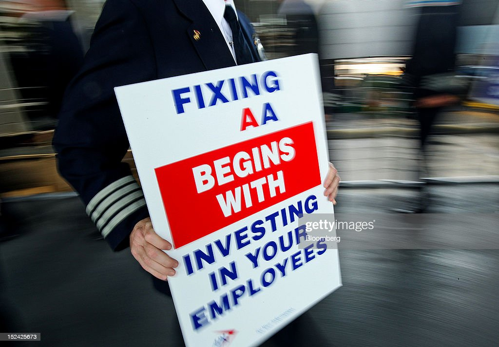 American Airlines Inc. pilot holds a sign while picketing at O'Hare International Airport in Chicago, Illinois, U.S., on Thursday, Sept. 20, 2012. American Airlines' on-time performance tumbled to 54 percent amid flight cancellations and delays that the carrier blames on a pilot shortage and increased maintenance issues. Photographer: Tim Boyle/Bloomberg via Getty Images