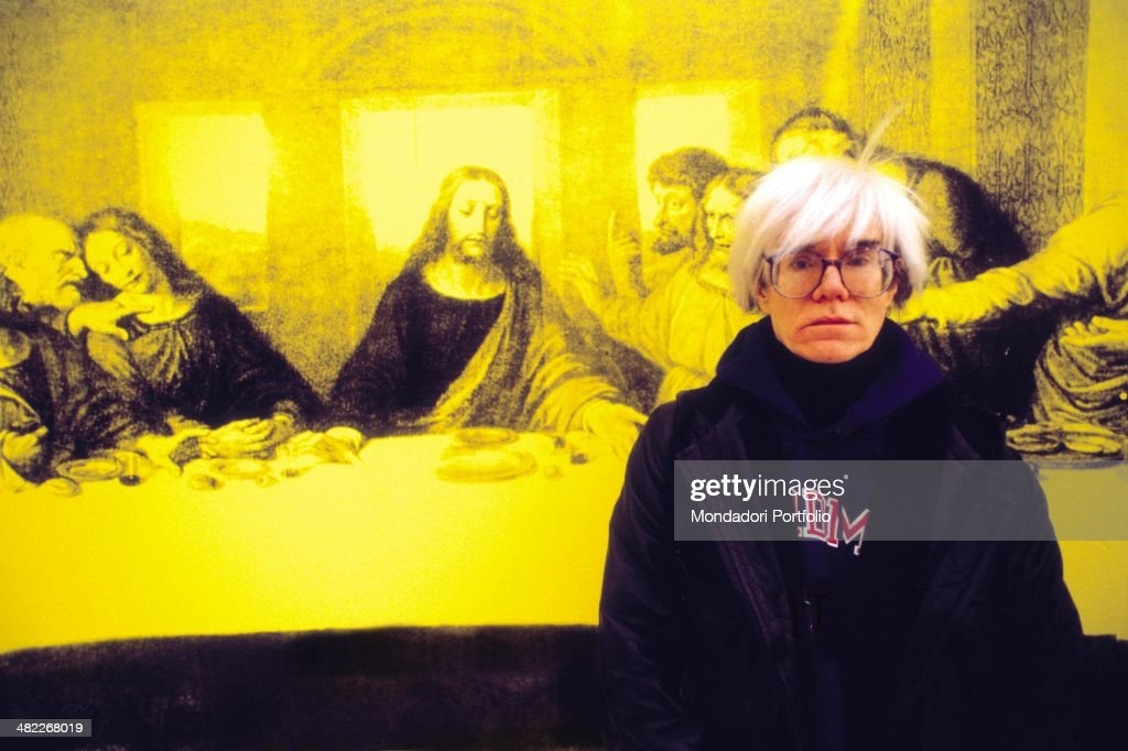 American all-round artist <a gi-track='captionPersonalityLinkClicked' href=/galleries/search?phrase=Andy+Warhol&family=editorial&specificpeople=123830 ng-click='$event.stopPropagation()'>Andy Warhol</a>, icon of the Pop Art Movement, posing seriously in front of The Last Supper, a personal interpretation the American artist gave of Leonardo da Vinci's Il Cenacolo, realized 1986, belonging to a series dedicated to Leonardo's masterpiece set up in palazzo delle Stelline; the work holds the spirit of Warhol's artistic Weltanschauung, demystifying the artwork in order to deprive it of its uniqueness and no repeatibility. Milan (Italy), 1987.