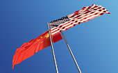 American and Chinese flags are waving with wind at opposite directions on a blue sky. Low angle view. Dispute and conflict concept. Horizontal composition with copy space. Great use for China and Unit