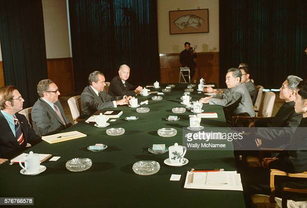 American and Chinese political leaders sit on opposite sides of a table at a meeting during President Richard Nixon's trip to China On the right are...