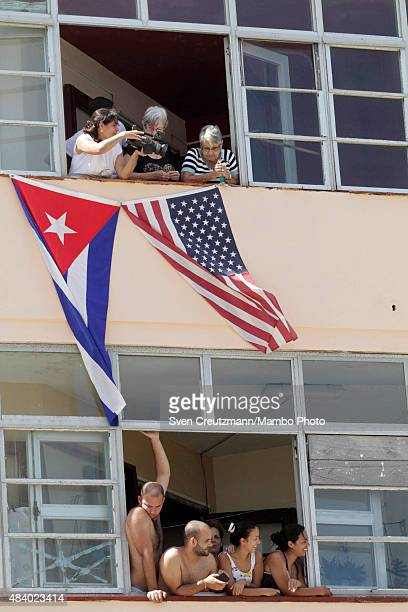 American and Cuban flags hang out of a window as people follow the flagraising ceremony led by US secretary of State John Kerry on August 14 in...