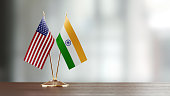 American and Indian flag pair on desk over defocused background. Horizontal composition with copy space and selective focus.