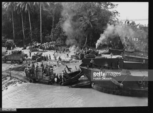 American and New Zealand troops use caterpillar tractors to unload craft at a beach on the Green Islands 130 miles east of the Japaneseheld Rabaul on...
