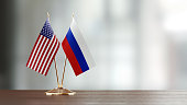 American and Russian flag pair on desk over defocused background. Horizontal composition with copy space and selective focus.