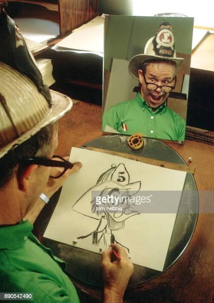 American animator Ward Kimball makes faces in a mirror as he draws cartoon character expressions at the Disney Studios Burbank California 1962