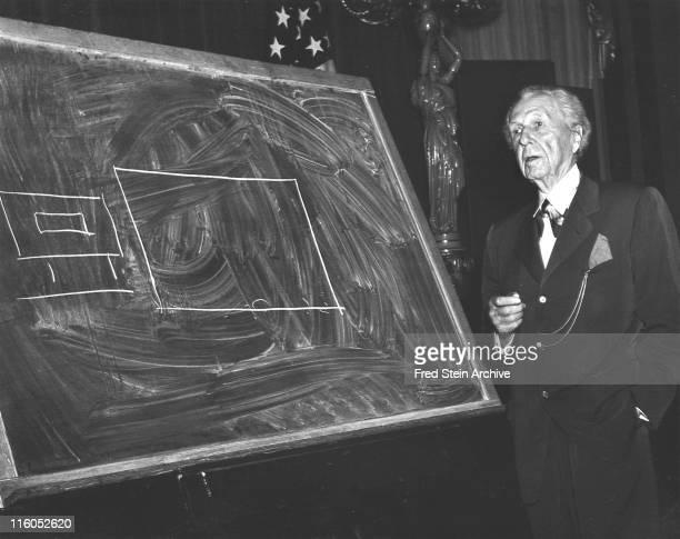 American architect Frank Lloyd Wright stands beside a diagram drawn on a chalkboard New York New York 1952