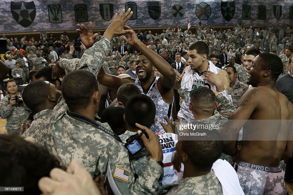 American Armed Forces personnel celebrate victory with Mike Moser #0 of the Oregon Ducks after they defeated the Georgetown Hoyas during the Armed Forces Classic at United States Army Garrison-Humphreys on November 9, 2013 in Pyeongtaek, South Korea.