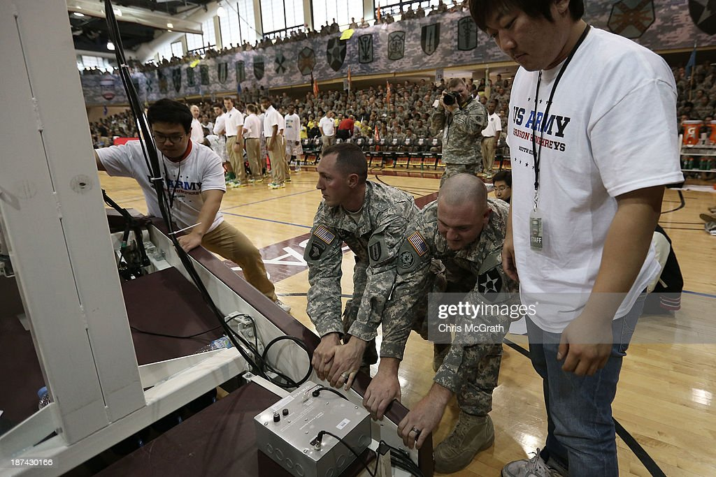 American Armed Forces personnel help to move the basket back into place after it moved following a slam dunk in the game between the Georgetown Hoyas and the Oregon Ducks during the Armed Forces Classic at United States Army Garrison-Humphreys on November 9, 2013 in Pyeongtaek, South Korea.