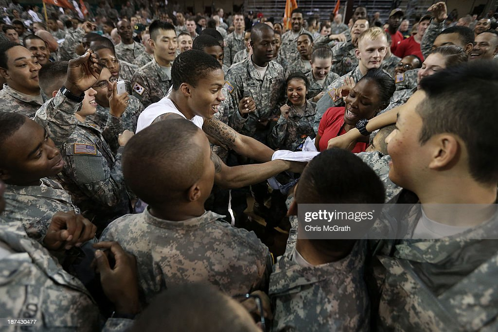 American Armed Forces personnel pull the uniform off Joseph Young #3 of the Oregon Ducks after they defeated the Georgetown Hoyas during the Armed Forces Classic at United States Army Garrison-Humphreys on November 9, 2013 in Pyeongtaek, South Korea.
