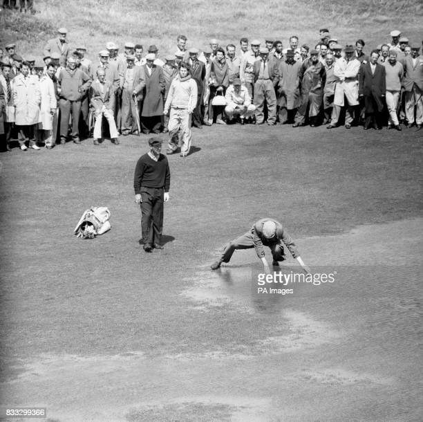 American Arnold Palmer looks on as his caddie fishes for his ball in one of the large pools of water left by overnight rainstorms on the sixth...