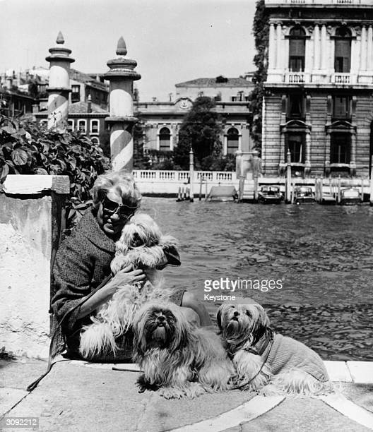American art collector and millionairess Peggy Guggenheim with her pet dogs outside her eighteenth century Venetian palace on the Grand Canal