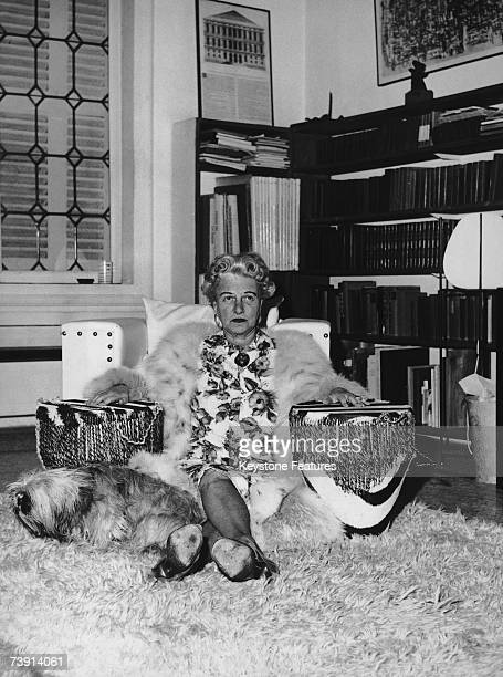 American art collector Peggy Guggenheim at her home in Venice with one of her dogs and a pair of drums December 1961