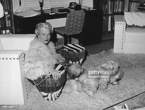 American art collector Peggy Guggenheim at her home in Venice with her dogs and a pair of drums December 1961
