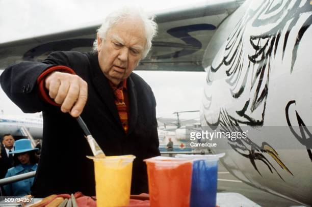American artist Alexander Calder paints the fuselage of a Boeing 727–291 passenger plane as a commission from Braniff International Airways Dallas...