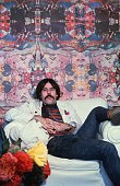 American artist and designer Peter Max sits in an armchair in front of one of his psychedelic murals at home