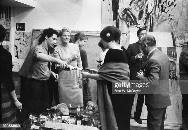 American artist and film director Alfred Leslie pours a drink for a guest at his loft party New York New York March 28 1960