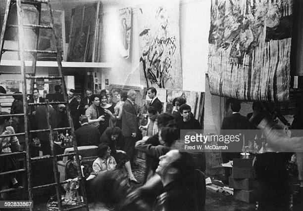 American artist and film director Alfred Leslie talks to guests at his loft party New York New York March 28 1960