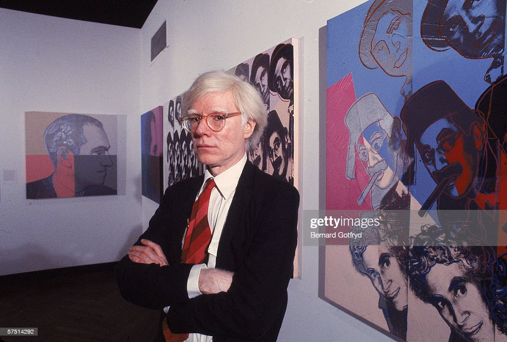 American artist <a gi-track='captionPersonalityLinkClicked' href=/galleries/search?phrase=Andy+Warhol&family=editorial&specificpeople=123830 ng-click='$event.stopPropagation()'>Andy Warhol</a> poses in front of his screenprints of the Marx Brothers and George Gershwin, part of his series 'Ten Portraits of Jews of the Twentieth Century' (1980), 1980s.