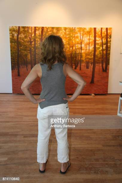 American artist April Gornik stands hands on her hips as she looks at a large painting in her studio Sag Harbor New York 2011