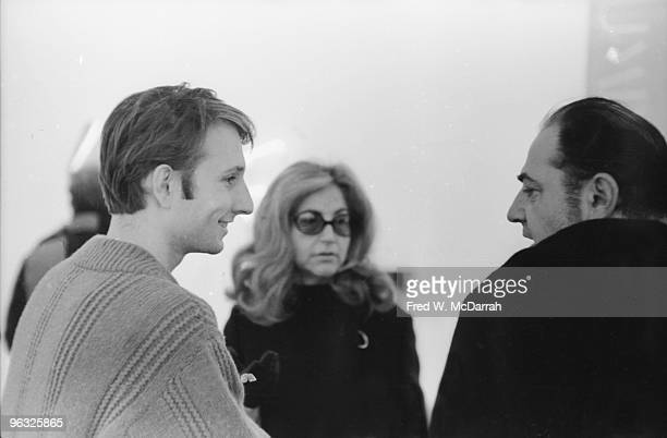 American artist Bruce Nauman speaks with businessman and art collector Robert C Scull and his wife Ethel Scull at teh Leo Castelli Gallery New York...